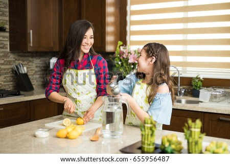Portrait of a cute young single mom and her daughter making lemonade and having a good time together in the kitchen