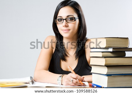 Portrait of a cute young student girl with large pile of books.
