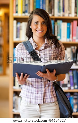 Portrait of a cute young student holding a book in the library