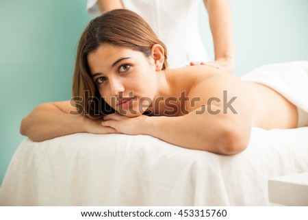 Portrait of a cute young woman relaxing at a spa and getting a massage