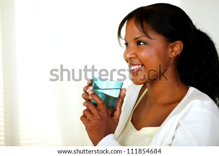 Portrait of a cute young woman smiling and drinking fresh water while looking to her right. With copyspace. - stock photo