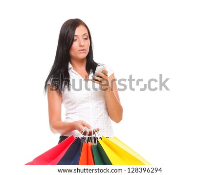 portrait of a cute young woman speaking on the mobile while holding shopping bags against white background