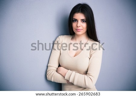 Portrait of a cute young woman with arms folded standing over gray background. Looking at camera.