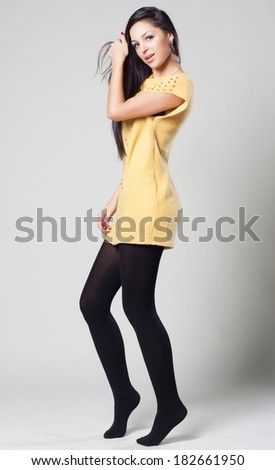 Portrait of a dancing young woman in yellow sweater. fashion concept and style. Spring clothes.  - stock photo