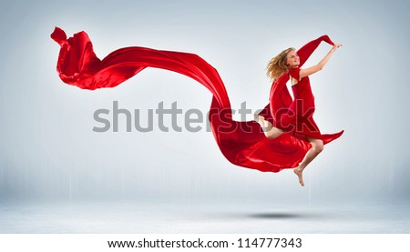 Portrait of a dancing young woman with red fabric