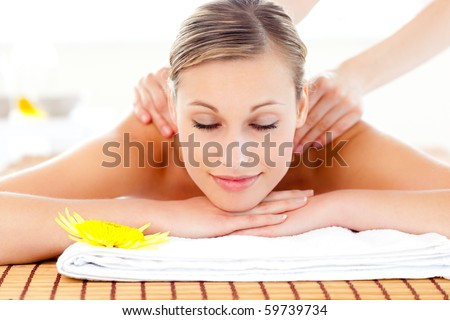 Portrait of a delighted woman lying on a massage table in a health spa - stock photo