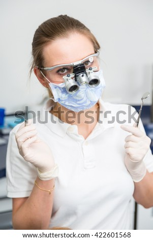 Portrait of a dentist with magnifying loupes and surgical mask - stock photo