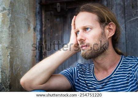 Portrait of a depressed man in a run-down building - stock photo