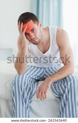Portrait of a depressed man sitting on his bed while looking at the camera - stock photo