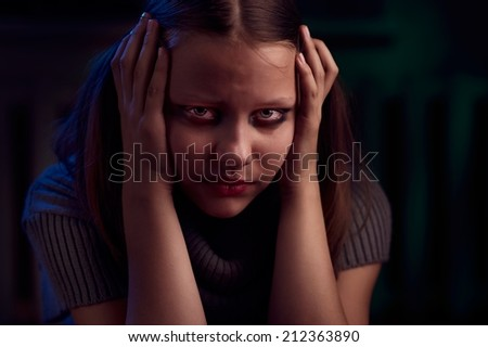 Portrait of a depressed teen girl sits and cries - stock photo
