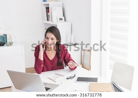 Portrait of a designer working home on new ideas. A dark braided hair woman is sitting at a white table in casual clothes, she is talking on her phone, looking at her laptop and smiling - stock photo