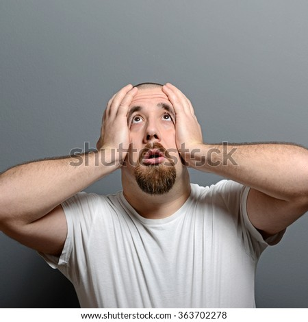Portrait of a desperate man in shock against gray background - stock photo