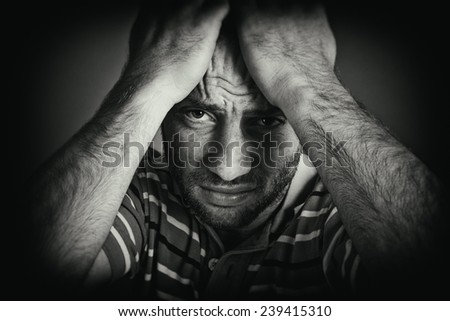 Portrait of a desperate young man with head in hands, looking at the camera. Black and white style picture. - stock photo