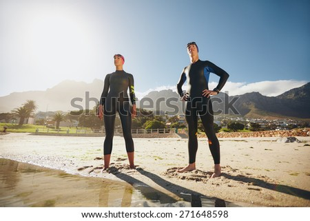 Portrait of a determined male and female triathletes looking into the distance. Young man and woman standing at the beach wearing wetsuit ready for triathlon competition. - stock photo