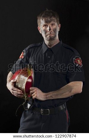Portrait of a dirty fireman holding his helmet at his side - stock photo