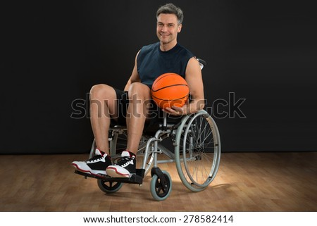 Portrait Of A Disabled Player On Wheelchair Holding Basketball - stock photo