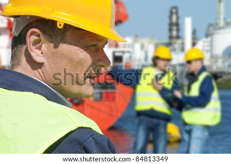 Portrait of a docker in front of a harbor scene with two of his coworkers out of focus in the background - stock photo