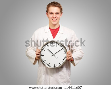 Portrait of a doctor holding a clock on grey background