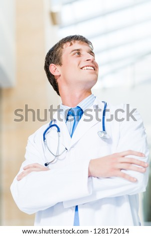 Portrait of a doctor standing in the office and crossed his arms - stock photo