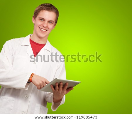 Portrait of a doctor using a tablet on green background