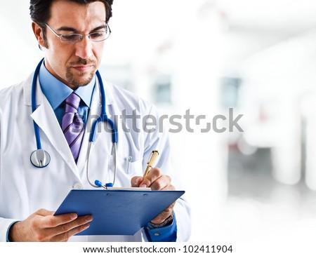 Portrait of a doctor writing a prescription - stock photo