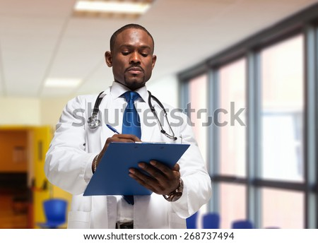 Portrait of a doctor writing on a clipboard - stock photo