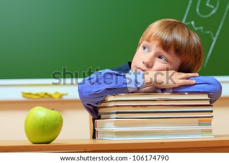 Portrait of a dreaming schoolboy in a classroom. - stock photo