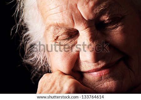 Portrait of a dreaming senior woman sitting with closed eyes. Over black background.