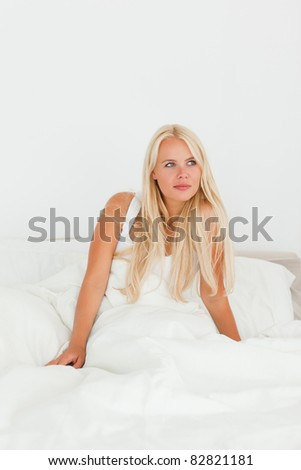 Portrait of a dreaming woman waking up while sitting on her bed - stock photo