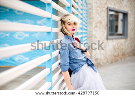 Portrait of a dreamy blond girl with short hair, bright pink lips and blue eyes wearing blue denim shirt,grey tulle skirt and marsala backpack leaning on blue and white stripes fence on the background - stock photo