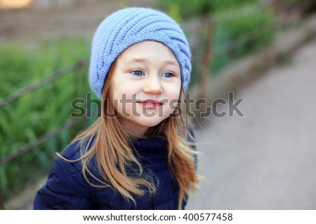 Portrait of a  dreamy kid girl in blue hat with blue eyes outdoor - stock photo