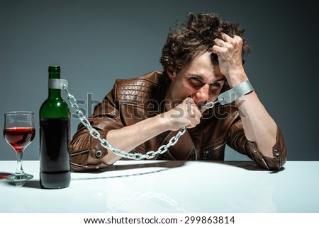 Portrait of a drunk and depressed man / photo of youth addicted to alcohol, alcoholism concept, social problem - stock photo