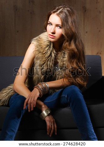 Portrait of a elegant woman sitting on a black sofa wearing a blue jeans and fur vest. - stock photo