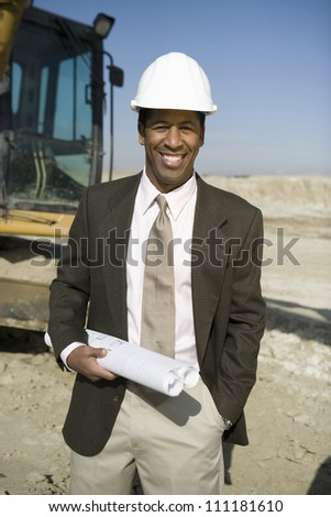 Portrait of a engineer wearing hard hat in front of a crane at construction site - stock photo