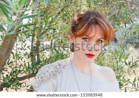 Portrait of a European girl with red hair, green eyes and red lips against the olive branch