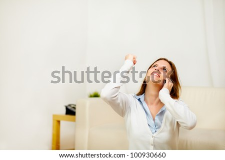 Portrait of a excited girl using a mobile phone while is celebrating a victory - stock photo