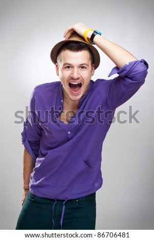 Portrait of a excited young guy wearing a hat  on white background - stock photo