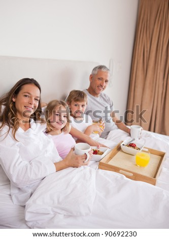 Portrait of a family having breakfast in a bedroom while looking at the camera - stock photo
