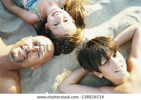 Portrait of a family lying on beach sand