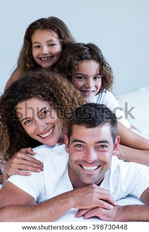 Portrait of a family lying on top of each other at home - stock photo
