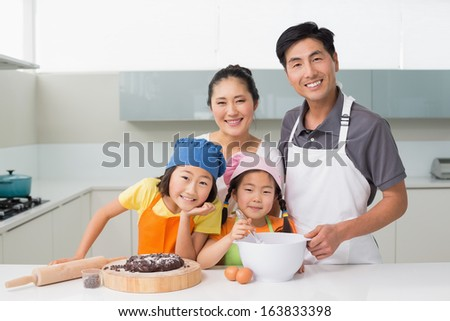 Portrait of a family of four preparing cookies in the kitchen at home