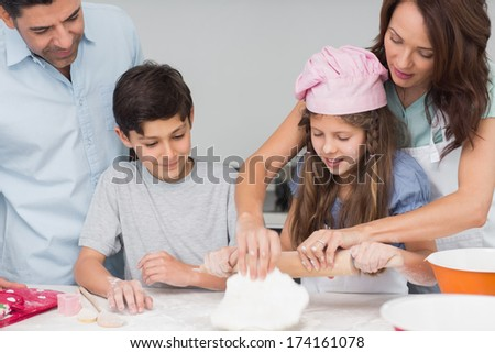 Portrait of a family of four preparing cookies in the kitchen at home - stock photo