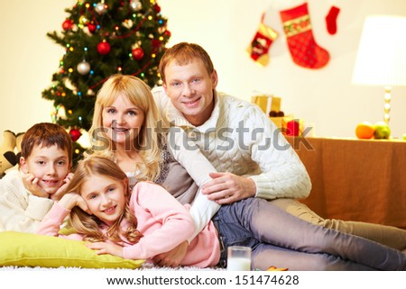 Portrait of a family of four relaxing on a Christmas day - stock photo