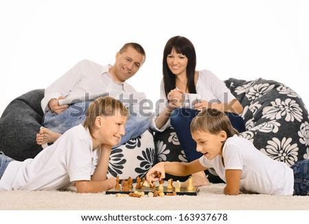 Portrait of a family playing chess at carpet
