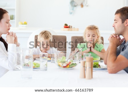Portrait of a family praying together during the lunch in the kitchen - stock photo