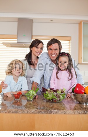 Portrait of a family preparing a salad in a kitchen - stock photo