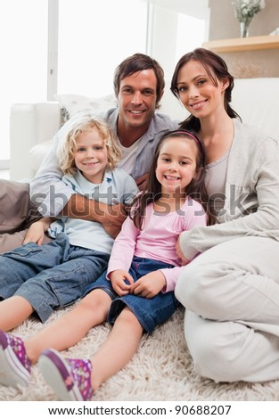 Portrait of a family relaxing in their living room while looking at the camera - stock photo