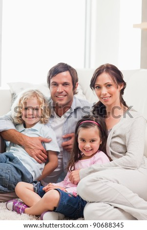 Portrait of a family relaxing on a sofa while looking at the camera - stock photo