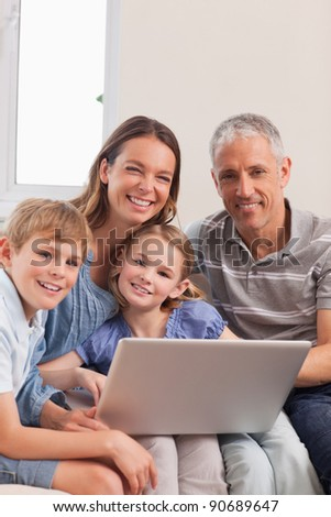 Portrait of a family sitting on a couch using a laptop in a living room - stock photo