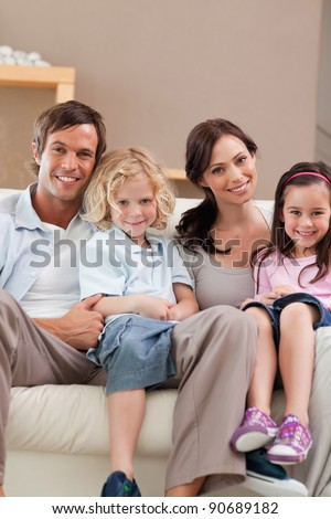 Portrait of a family watching television together in a living room